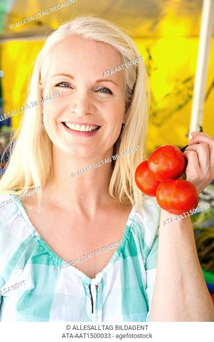 Woman choosing tomatoes on a weekly market