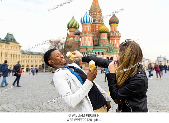 Russia, Moscow, multiracial couple eating icecream