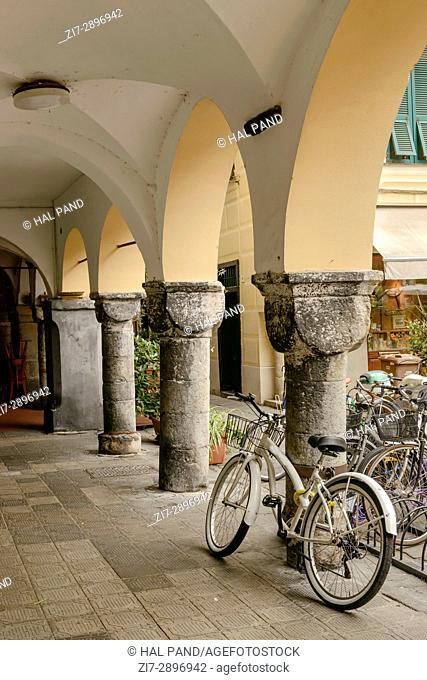 bicycle parked near stone pillar of medieval covered walkway, shot at Mediterranean little town of Chiavari, Genova, Liguria, Italy