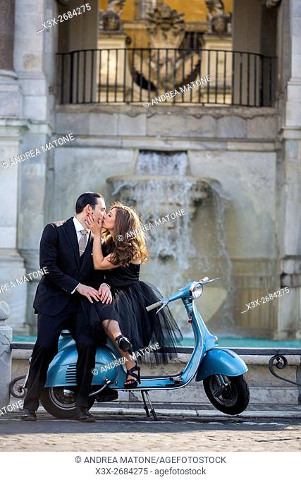 Couple kissing while sitting on a vespa scooter. Janiculum water fountain. Rome, Italy