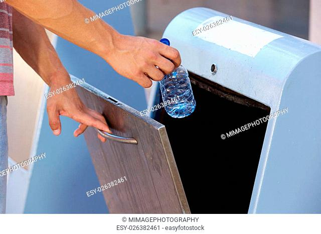 Close up man hand throwing away plastic bottle in recycling bin
