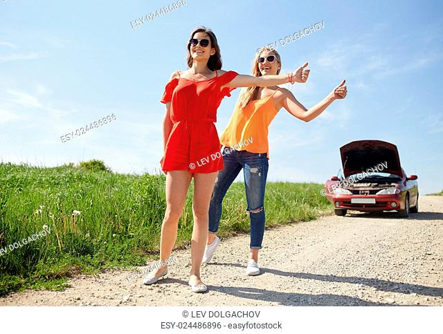 road trip, transport, travel, gesture and people concept - young women with broken car showing hitchhiking gesture asking for help at countryside