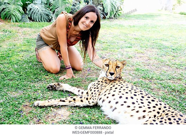 Namibia, Kamanjab, tourist petting a tame cheetah