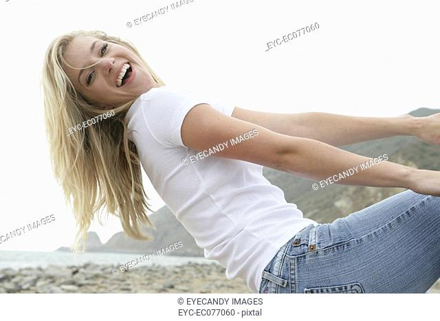 Carefree young woman laughing on the beach
