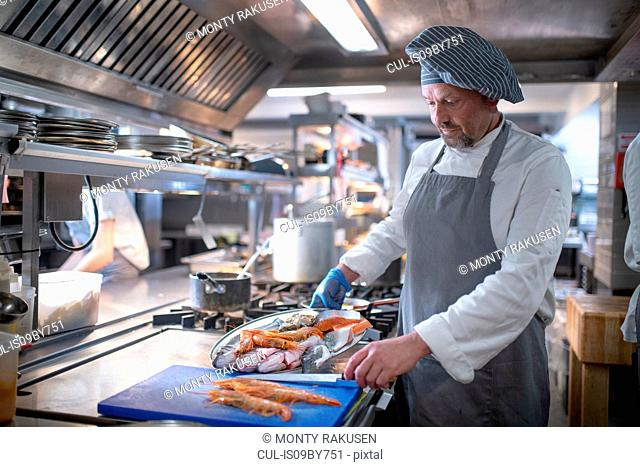Chef preparing seafood dish in Italian restaurant kitchen