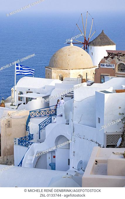 Traditional Greek flag with domed Orthodox Church overlooking the Aegean Sea in Oia Santorini Greece