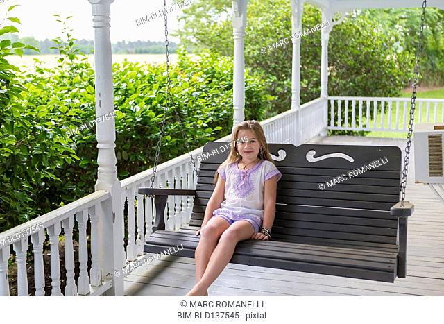 Caucasian girl relaxing in swing on porch