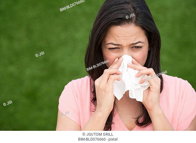 Hispanic woman blowing nose