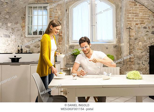Couple in kitchen eating fruit salad