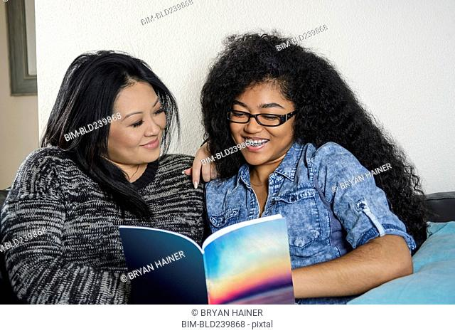 Smiling mother and daughter reading book