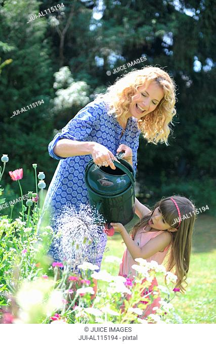 Mother and daughter watering flowers in garden