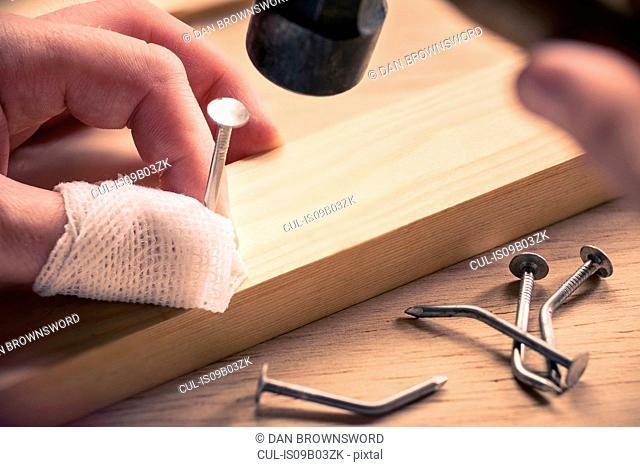 Bandaged finger holding nail on wood