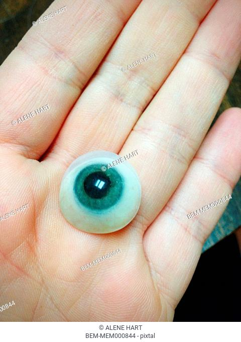 Close up of glass eye in hand