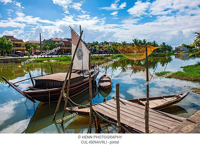 Wooden pier, fishing boats and fishing nets on river, Hoi An, Quang Nam Province, Vietnam