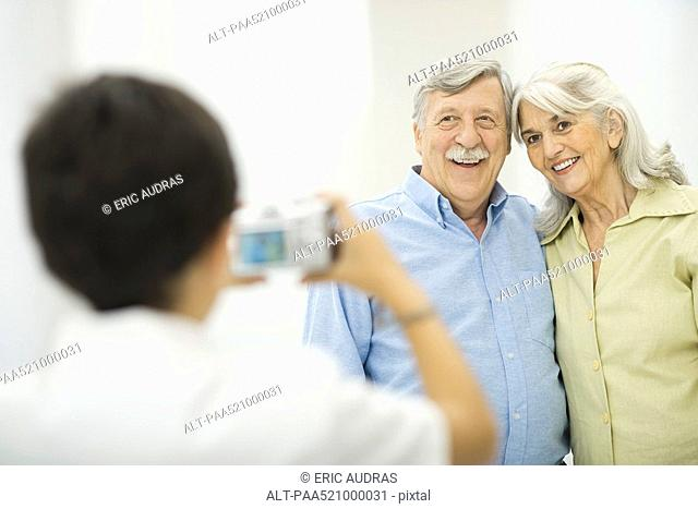 Grandson taking picture of grandparents with digital camera