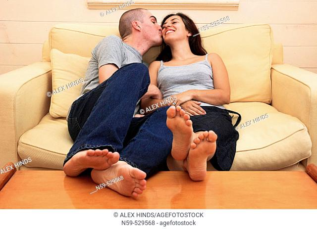 A happy young couple kissing on the sofa