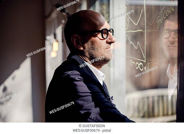 senior businessman brainstorming, drawing formulas on window pane