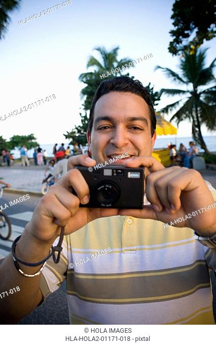 Mid adult man holding a camera