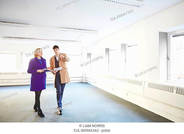 Colleagues walking through empty office