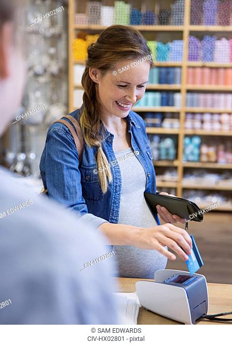 Pregnant woman using credit card reader in shop