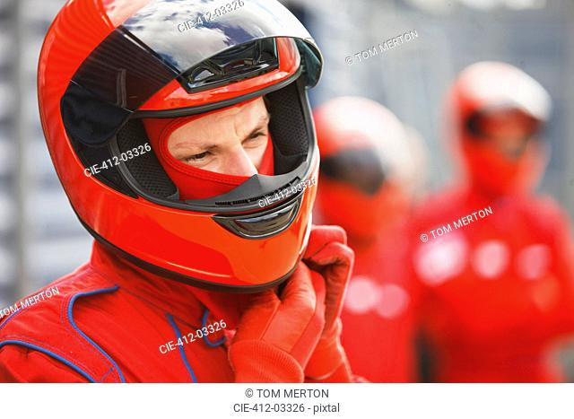 Racer tying on helmet on track
