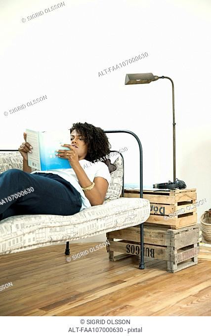 Woman lying on sofa reading book