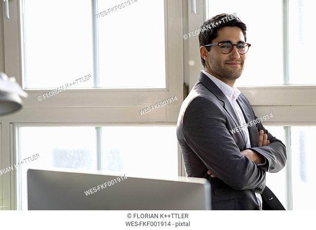 Businessman standing at the window with arms crossed