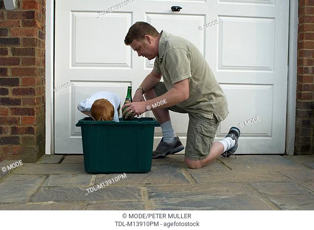 A father and son putting out recycling