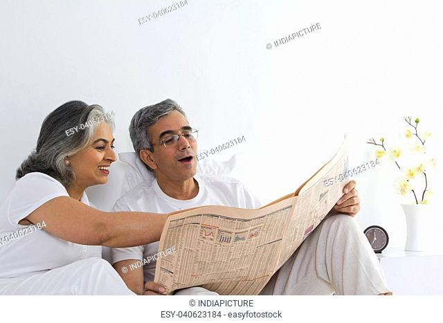 Husband and wife reading the newspaper