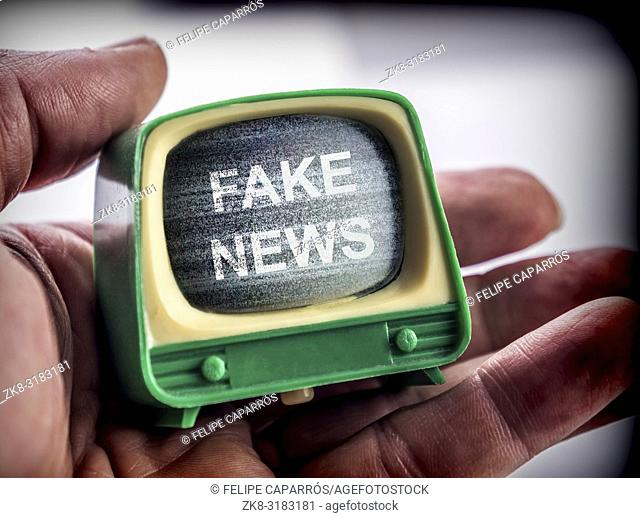 Hand holds miniature TV, fake news metaphor, conceptual image