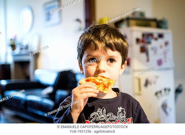 4 year old child eats a slice of pizza in the kitchen