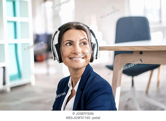 Portrait of smiling businesswoman in a loft listening music with headphones