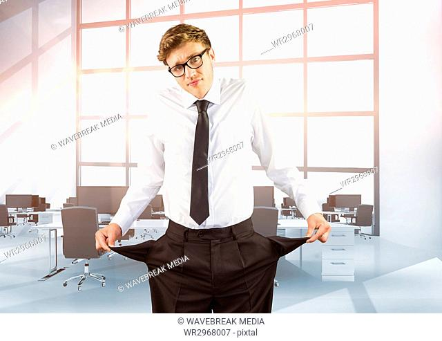 Businessman showing empty pockets while standing in office