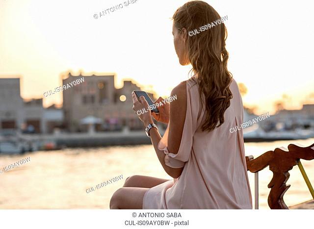 Woman reading smartphone texts on boat at Dubai marina, United Arab Emirates