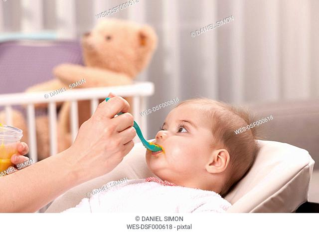 Mother's hand feeding baby girl