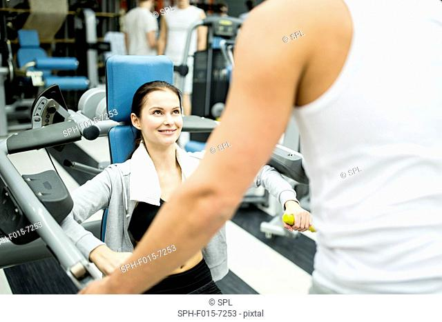 MODEL RELEASED. Young woman exercising with trainer in gym