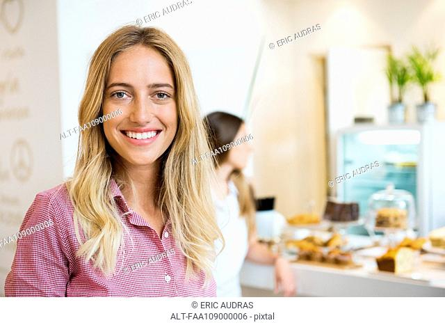 Young woman smiling cheerfully in bakery, portrait