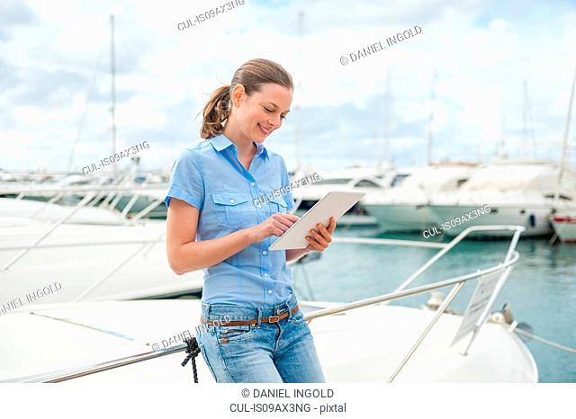 Woman leaning against marina yacht using digital tablet, Majorca, Spain