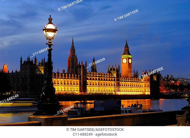 Big Ben clock tower and Houses of Parliament reflected in river Thames. London. England, UK,  at night showing river walkway
