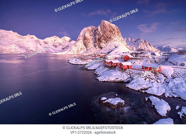The colors of dawn on snowy peaks and the frozen sea around the fishing village Hamnoy Nordland Lofoten Islands Norway Europe