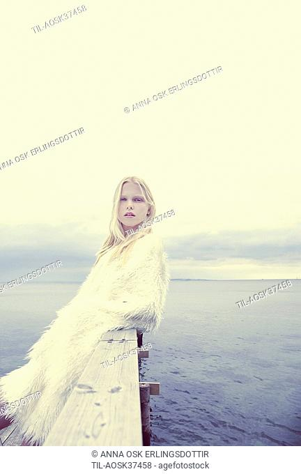 Female teenager with blonde hair wearing a whit fur coat standing by sea