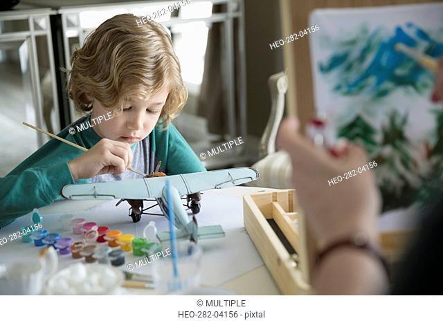 Boy painting model plane