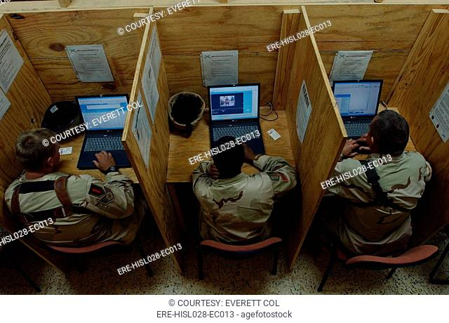 Soldiers and airmen in Iraq check their e-mail at Camp Caldwell Iraq. Nov. 19 2004. BSLOC-2011-12-282