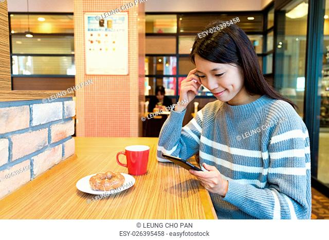 Woman use of mobile phone at coffee shop