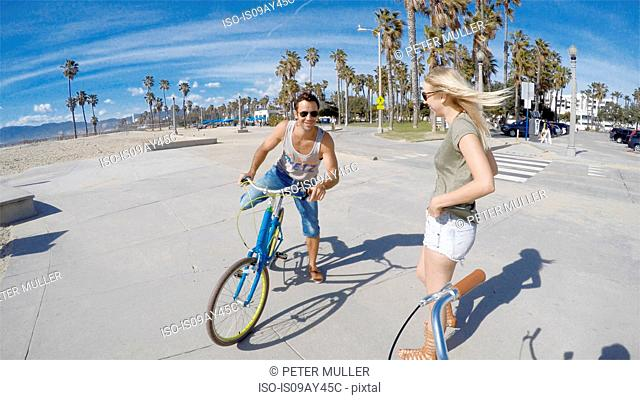 Portrait of young woman cycling at Venice Beach, California, USA
