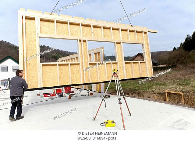 Europe, Germany, Rhineland Palantinate, Man installing and fixing wooden walls of prefabricated house