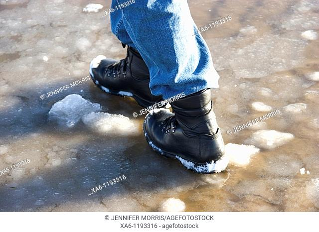 A man's booted feet as he walks on a frozen beach