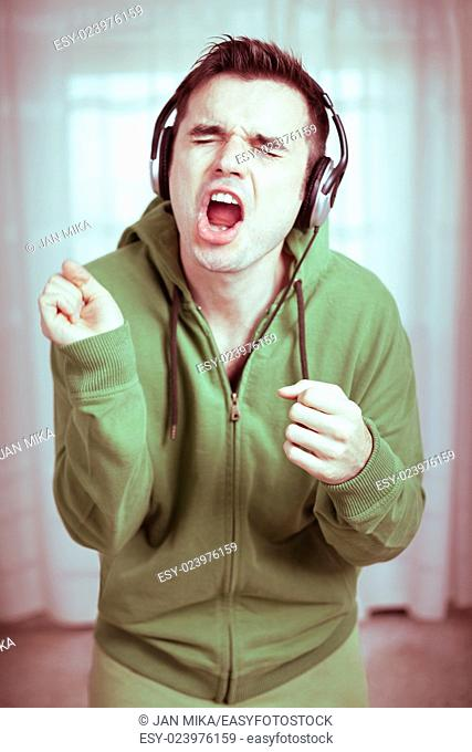 Crazy casual young man with headphones singing