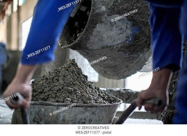 Worker mixing concrete in industrial pot factory