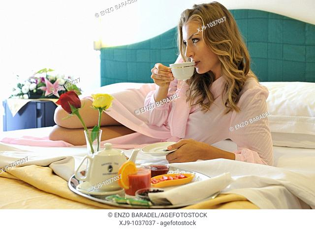 Young woman on bed in hotel room